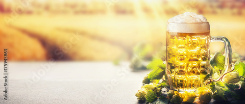 Fotografie, Obraz  Mug of beer with foam on table with hops at field nature background with sunbeam