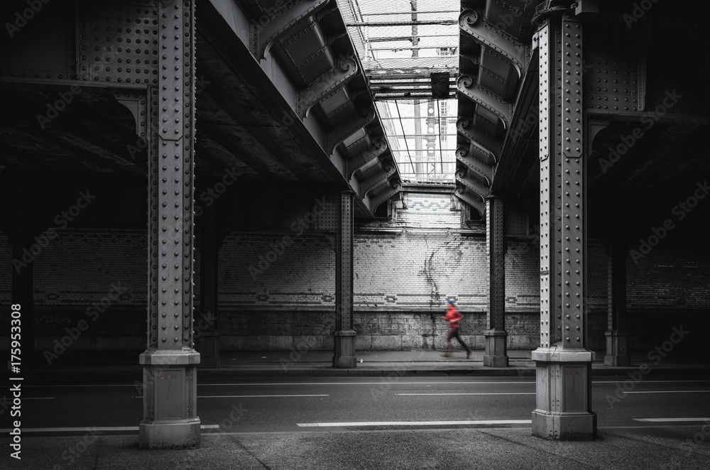 Fototapeta Woman running under an old railroad viaduct.