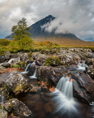 Picturesque waterfall by the river with Buacheille Etive Mor in the background surrounded with morning mist.
