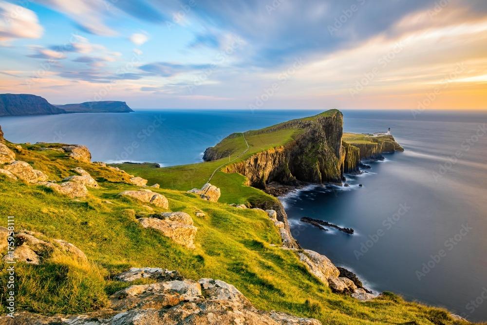 Fototapeta Neist Point Lighthouse on the Isle of Skye bathed in golden light from the setting sun.
