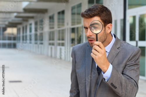 Private investigator looking through a magnifying glass Canvas Print
