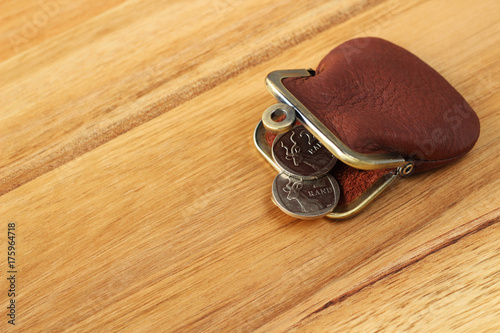 South African two rand coins and a small leather purse on a wooden table top. This image can be used to represent South African money.