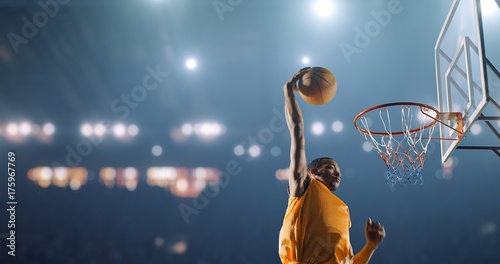 Photo  Basketball player performs a slam dunk on a sport background