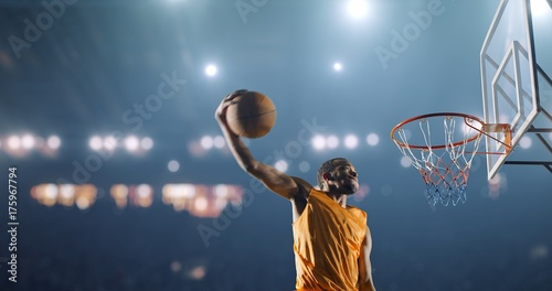 Basketball player performs a slam dunk on a sport background Canvas Print