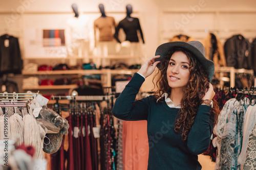 Plakat Młoda dorosła kobieta próbuje na kapeluszu w sklepie detalicznym.