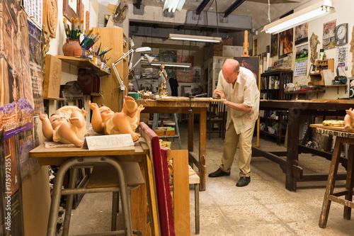 Maestro artesano trabajando en su taller de talla y restauración. Wallpaper Mural