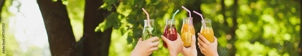 Fototapeta Group of people celebrate with detox juice cocktails on green nature background witn free space. Diet on the go, well being and weight loss, superfoods, health, vegetarian food concept
