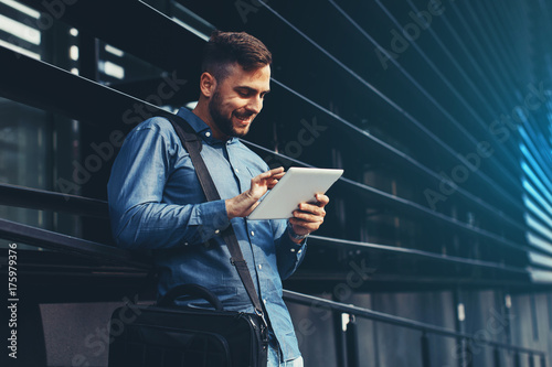 Handsome young man using digital tablet leaning against the wall