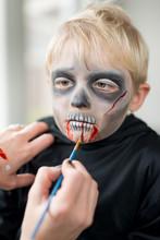 Mother Applying Little Boys Gory Halloween Costume Make Up