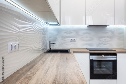 Obraz New bright modern kitchen with built in oven and chrome water tap and a wooden table top - fototapety do salonu