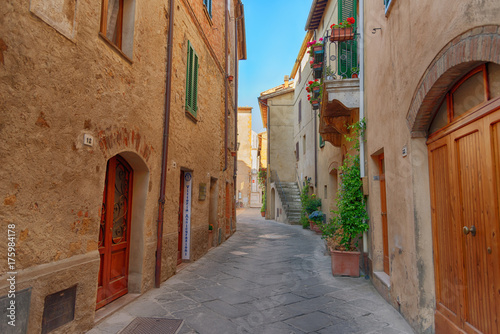 Fototapety, obrazy: Beautiful narrow street with sunlight and flowers in the small magical and old village of Pienza, Val D'Orcia Tuscany, Italy.