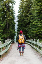 A Woman Walking Down A Trail Lined With Trees