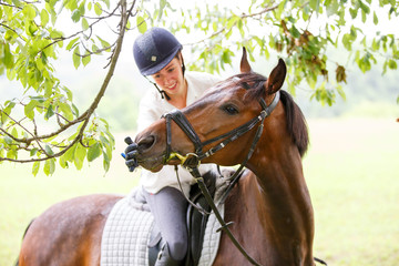 Young smiling rider woman touching lips of horse.
