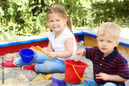 Fototapeta Cute little children playing in  sandbox, outdoors