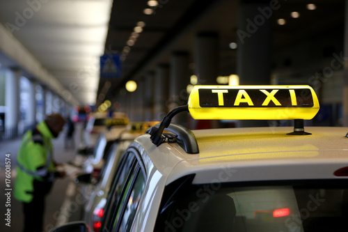 Zdjęcie XXL Znak taksówką na dachu samochodu z refleksji, wąż na lotnisku, człowiek rozdaje bilety
