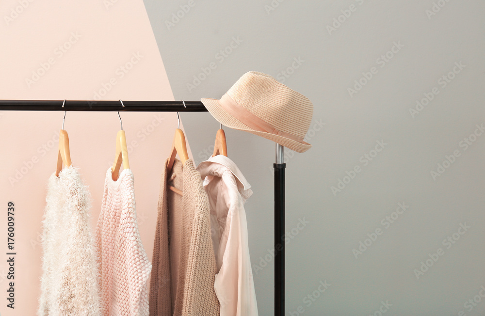 Fototapety, obrazy: Apricot and beige clothes on hangers against trendy color background