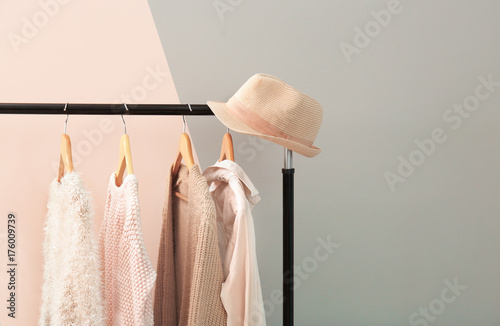 Fototapeta Apricot and beige clothes on hangers against trendy color background obraz