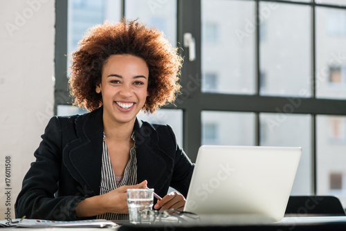 Fotografie, Tablou  Portrait of African American woman sitting at desk while working on laptop in th