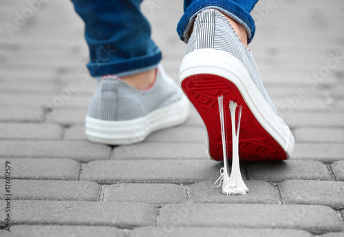 Foot stuck into chewing gum on street. Concept of stickiness