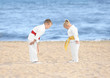canvas print picture - Little children performing ritual bow prior to practicing karate outdoors