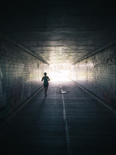Woman Running Through Tunnel Towards Bright Light