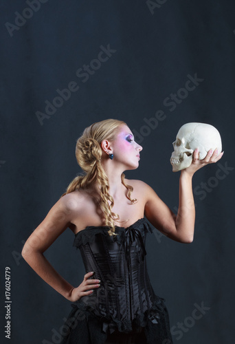 Fotografie, Obraz  Beautiful woman in black corset with a skull
