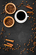 Ingredients for coffee. Roasted coffee beans and cinnamon on black background top view copyspace