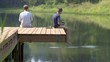 Two boys sitting on the end of a wooden jetty and fishing in a large pond surrounded by trees. Close view, 4K