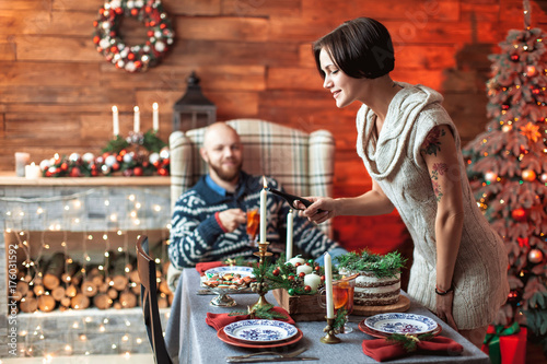 Foto op Plexiglas Caraïben Beautiful young couple cover the table in preparation for Christmas dinner in the beautifully decorated New Year interior with Christmas tree