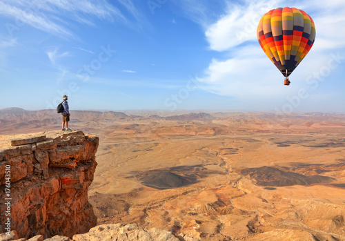 Cadres-photo bureau Marron Beautiful landscape of stony desert and rocks and colorful hot air balloon flight in the blue sky. Traveler is on the mountain top viewpoint