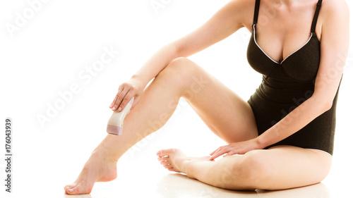 Plakat Kobieta goli jej nogi z elektryczną żyletką