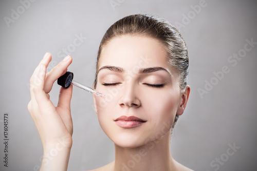 Plakat Kosmetyczny olej stosuje na twarzy młoda kobieta.