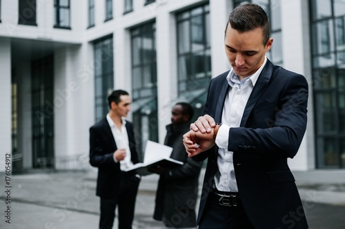 Valokuva  Young businessman in the foreground looks at the clock on the background of colleagues on a city street