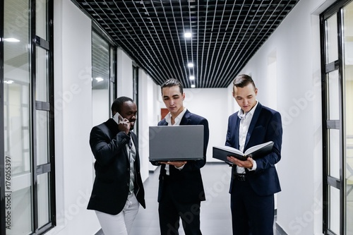 Obraz na plátne  Three businessman standing in modern office with laptop and Notepad