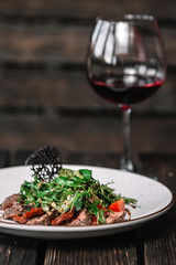 Glass of wine and salad with warm veal, sun dried tomatoes and arugula on dark wooden background