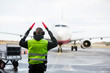 canvas print picture - Ground Crew Signaling To Airplane On Wet Runway