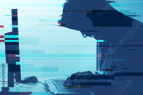 Fotografie, Obraz  Hooded computer hacker working on desktop PC computer