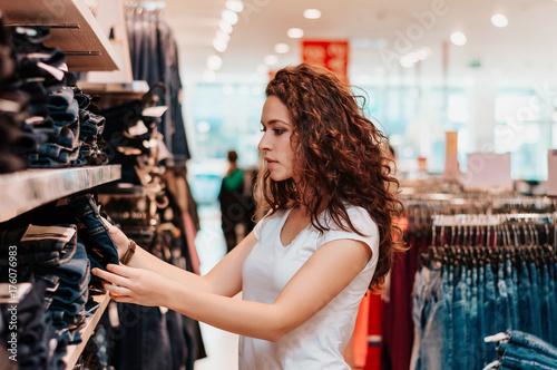 Plakat Młoda dziewczyna w sklepie kupuje ubrania.