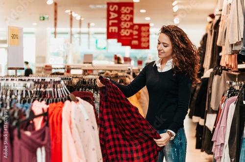 Zdjęcie XXL Brunetka kobieta klienta wybierając podstawowe ubrania w sklepie.
