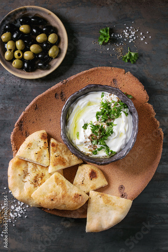 labneh middle eastern lebanese cream cheese dip with olive oil, salt, herbs served with olives, traditional pita bread on terracotta plate over dark texture metal background. Top view with space