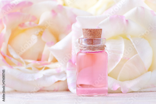 Fotografia  a glass bottle of essential oil and fresh rose flowers, selective focus