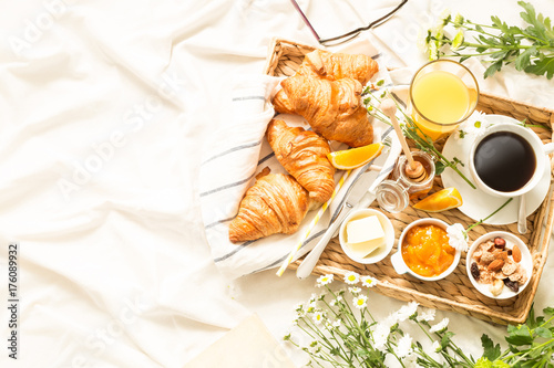 Fotografie, Obraz  Continental breakfast on white bed sheets - flat lay