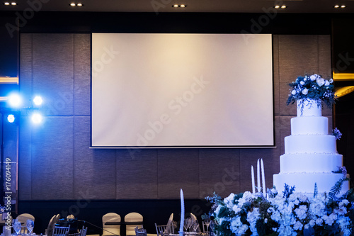 Photo Front view of wedding room with empty white projector screen