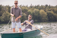 A Man Is Rowing A Rowboat While His Friend Is Fly Fishing From The Boat On A  Lake.