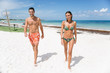 Young couple of man and woman walking on the sand of a tropical beach on vacation