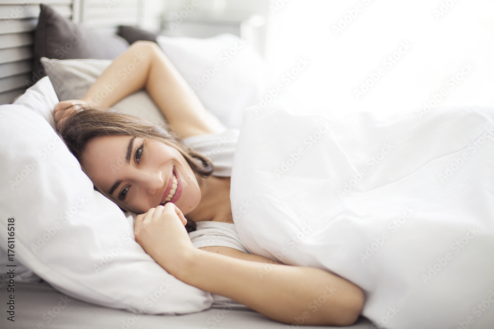 Fototapeta Happy morning. Portrait of a smiling pretty young brunette woman relaxing in white bed.