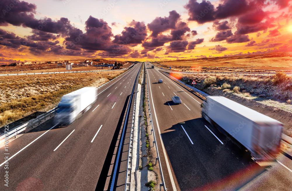 Fototapeta Camiones y autovia.Transporte internacional y logistica.Mercancia llegando a su destino por carretera. Industria del transporte