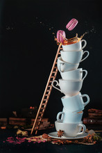 Tower Of White Coffee Cups With A Ladder, Macaroons, Splash And Coffee Drops On A Dark Background. Indulgence Concept. Action Food Photography.