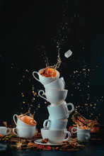 Stack Of White Coffee Cups With Dynamic Splashes And Coffee Drops On A Dark Background. Kitchen Mess And Mad Tea Time Concept. Action Food Photography.