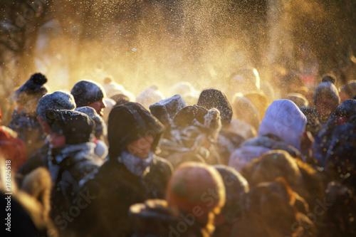 Zdjęcie XXL Zamazany tłum ludzi w winter park. Ładne, ciepłe światło z cząstkami śniegu